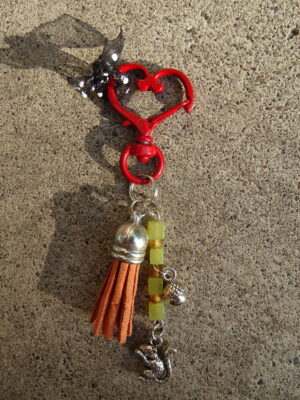 A keychain on a swivel red heart; burnt orange tassel; squirrel and acorn charms on a metal rod; the metal rod has green and orange beads.