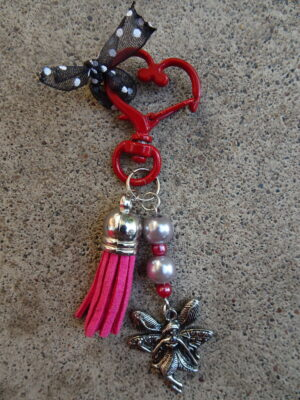 A red heart swivel keychain with a pink tassel, silver and pink beads on a metal rod, and fairy charm hanging at the bottom.