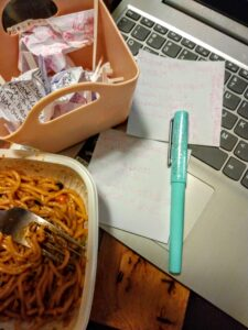 A bowl of noodles with notes and a fountain pen. and a small container of crumpled notes, on a laptop keyboard.