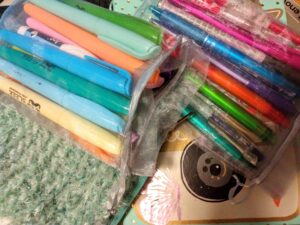 Highlighters and pens in cinch bags, on top of a knitted pencil case, and notebook with camera and butterfly stickers peaking from underneath.